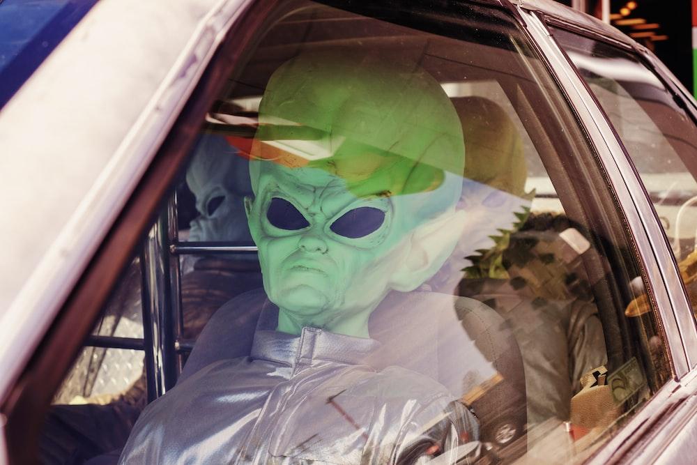 man in green mask inside car