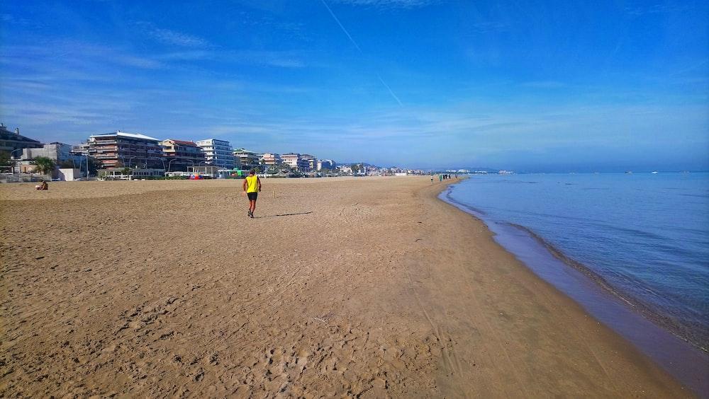 man in yellow shirt walking on beach during daytime