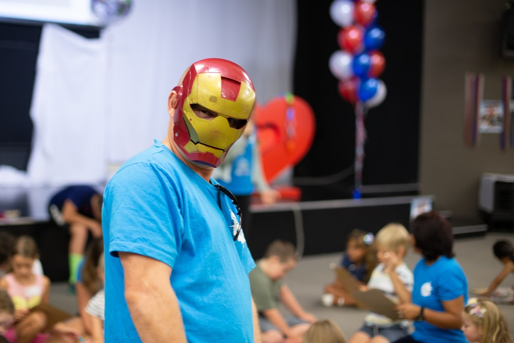 man in blue crew neck t-shirt wearing red yellow and blue mask