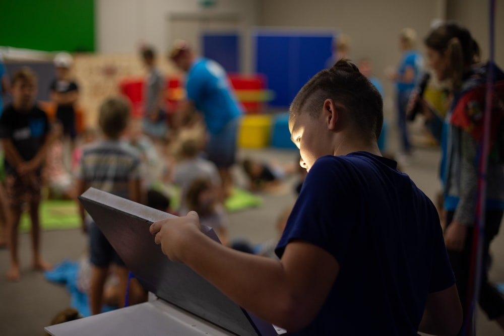 boy in black t-shirt holding tablet computer