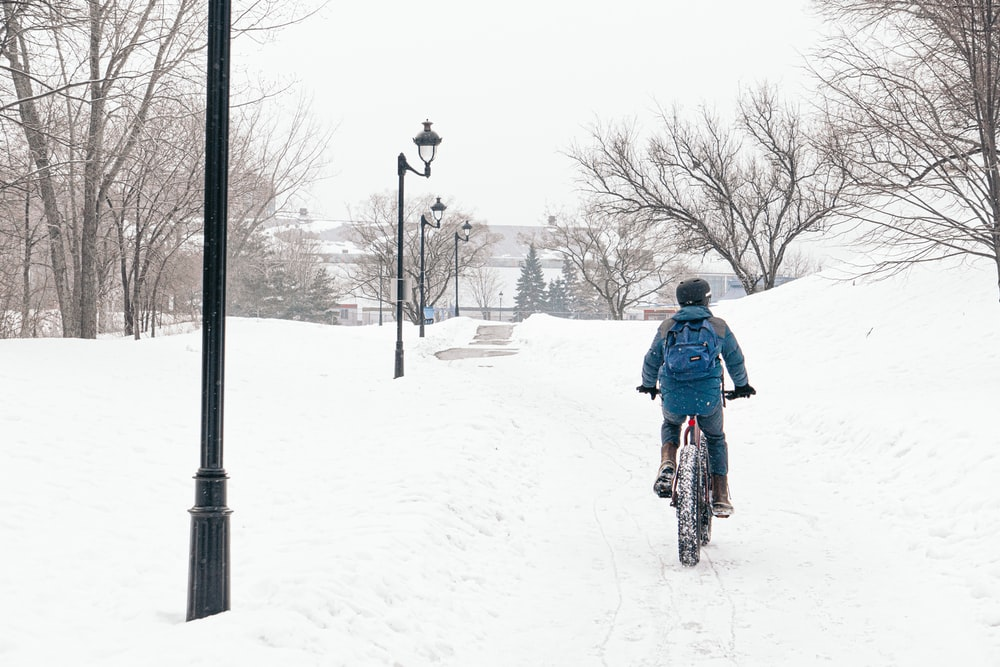 man in blue jacket riding bicycle on snow covered ground during daytime