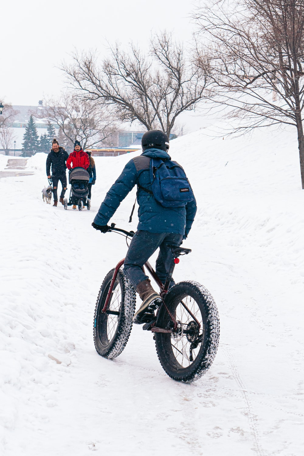 man in blue jacket riding on black bmx bike on snow covered ground during daytime