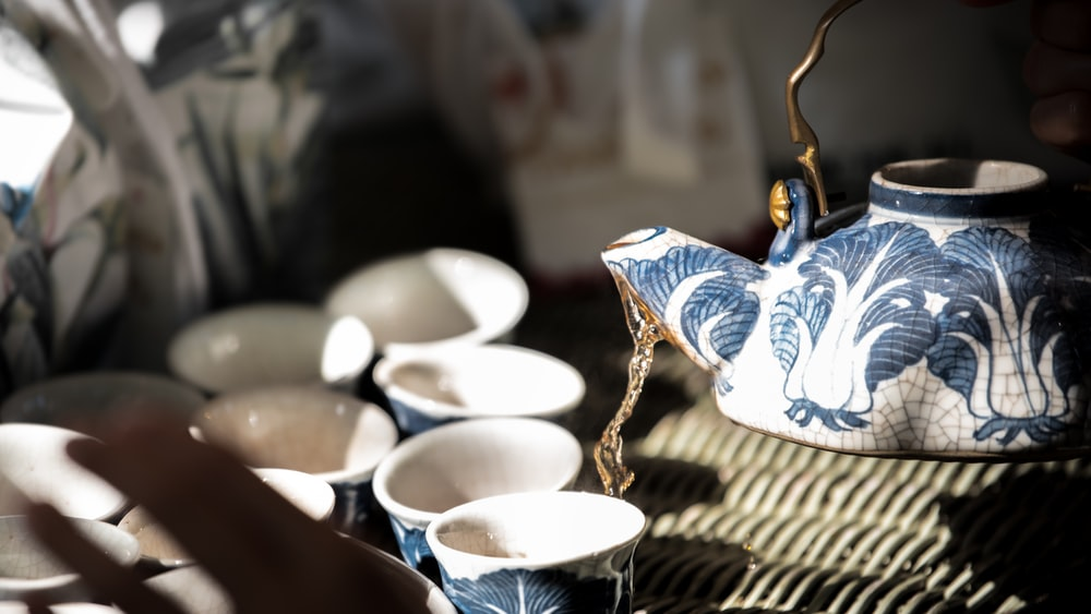white and blue ceramic teacup on brown woven table mat
