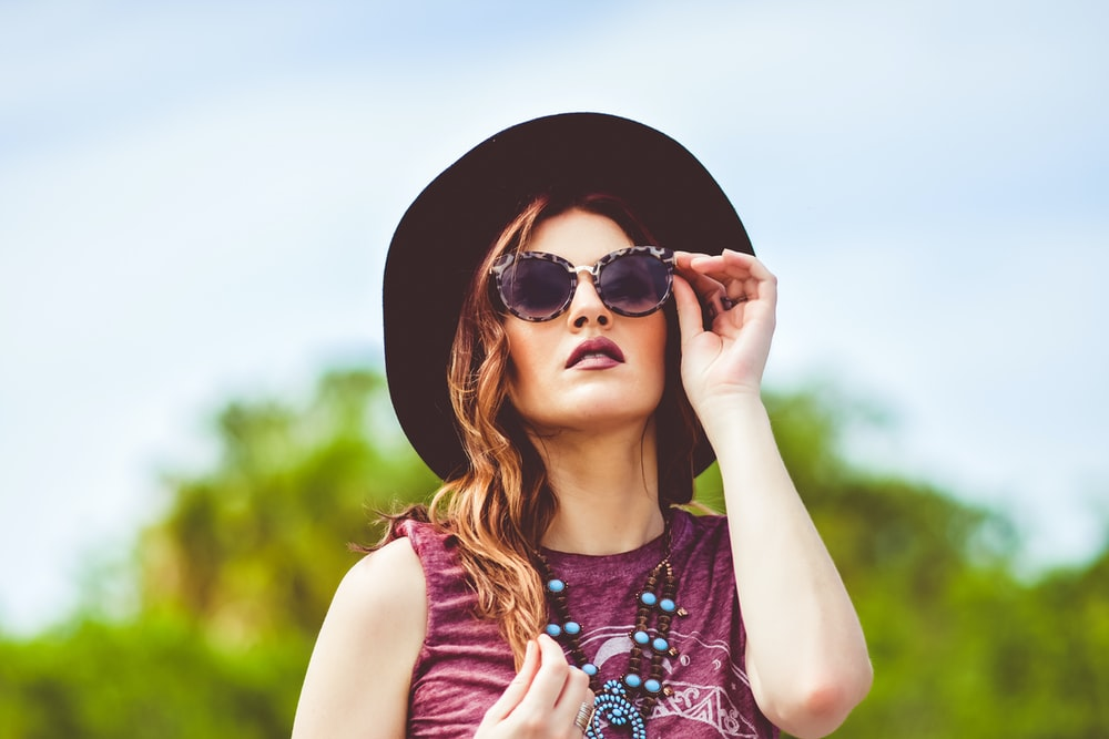 girl in purple and white floral tank top wearing black sun hat and black sunglasses