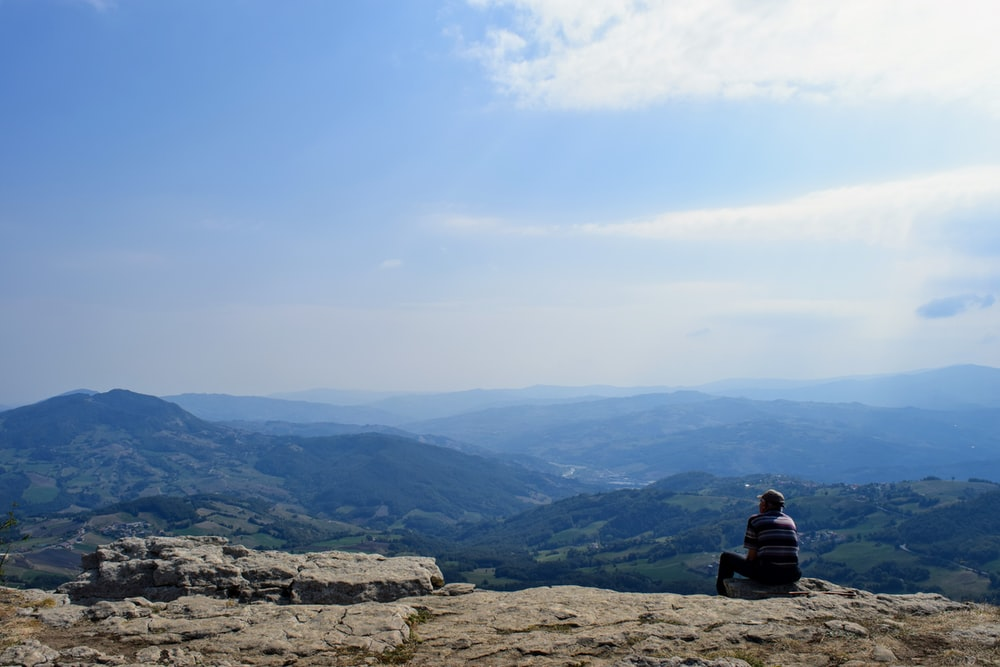 person sitting on rock formation looking at mountains during daytime