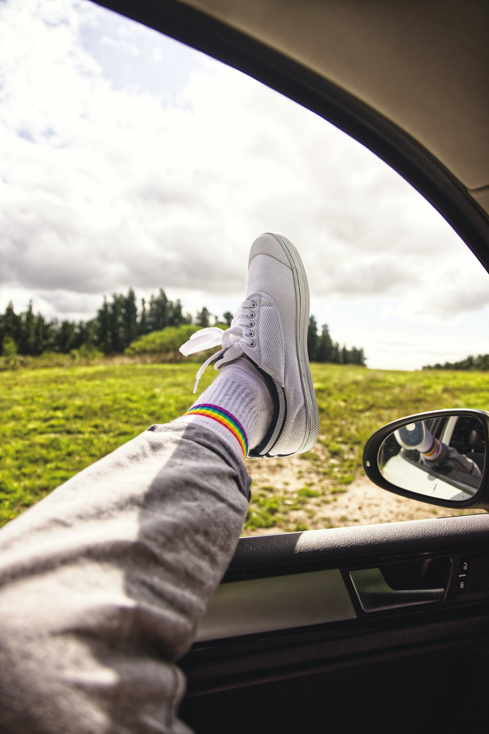 person in gray pants and gray sneakers sitting inside car during daytime