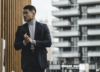 man in black suit standing on sidewalk during daytime