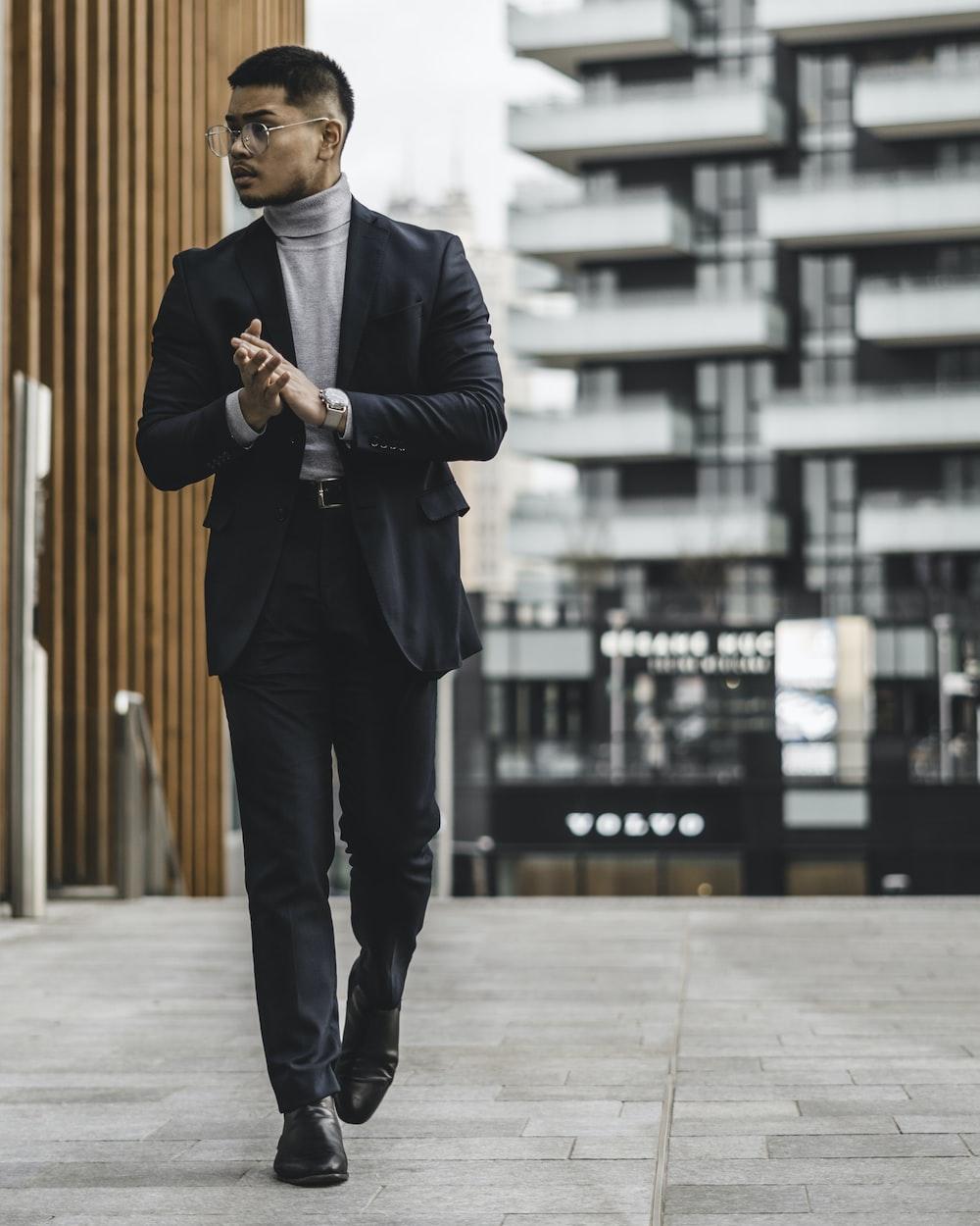昼間の歩道に立っている黒いスーツの男