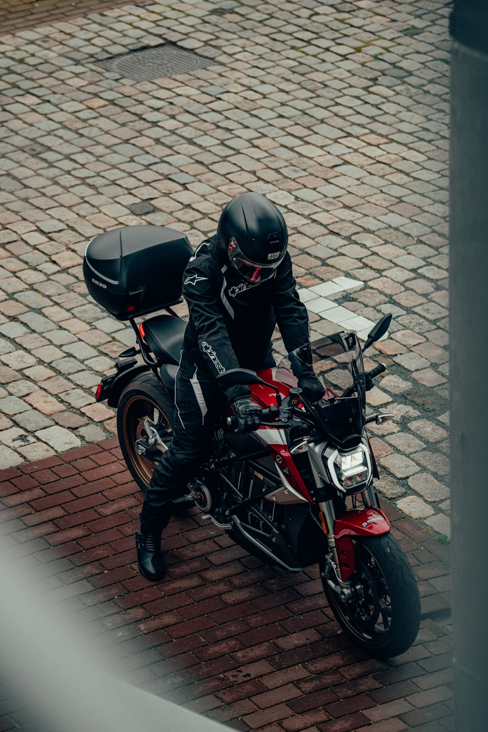 man in black leather jacket and black helmet riding red and black motorcycle
