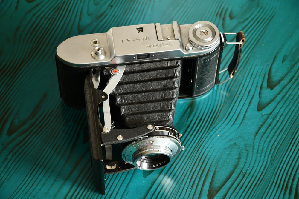 black and silver camera on green textile