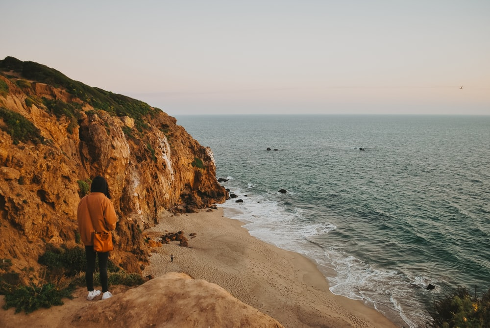 2 person standing on brown rock formation near body of water during daytime