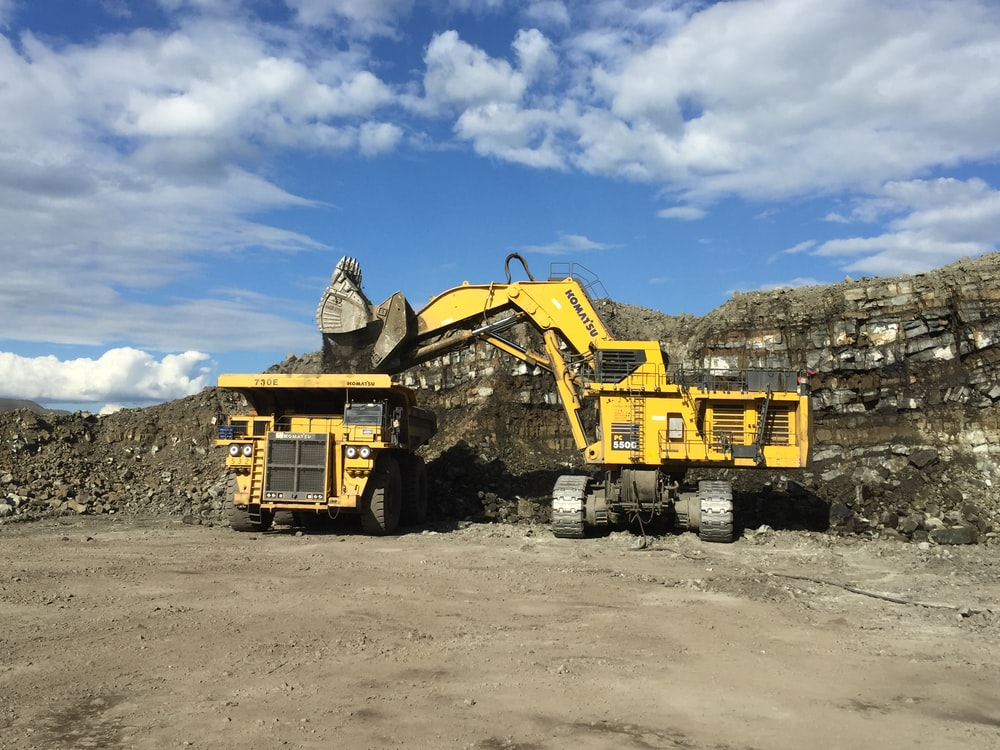 yellow and black heavy equipment on brown sand under blue sky during daytime