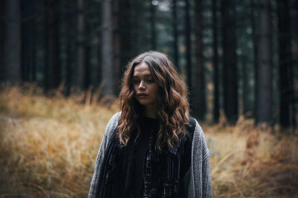woman in black jacket standing in forest during daytime