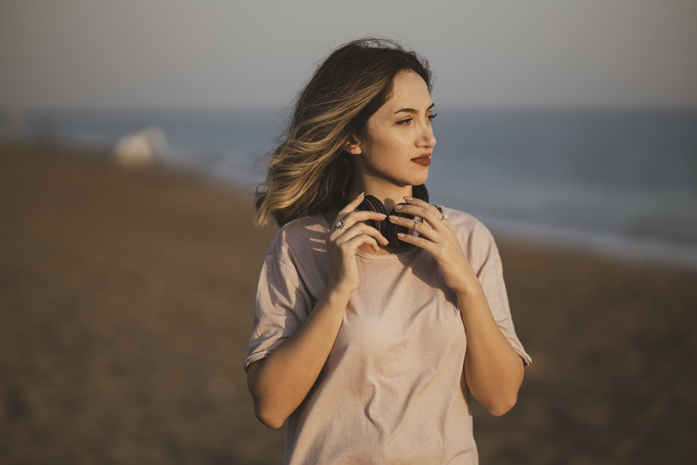 woman in white shirt standing on beach during daytime
