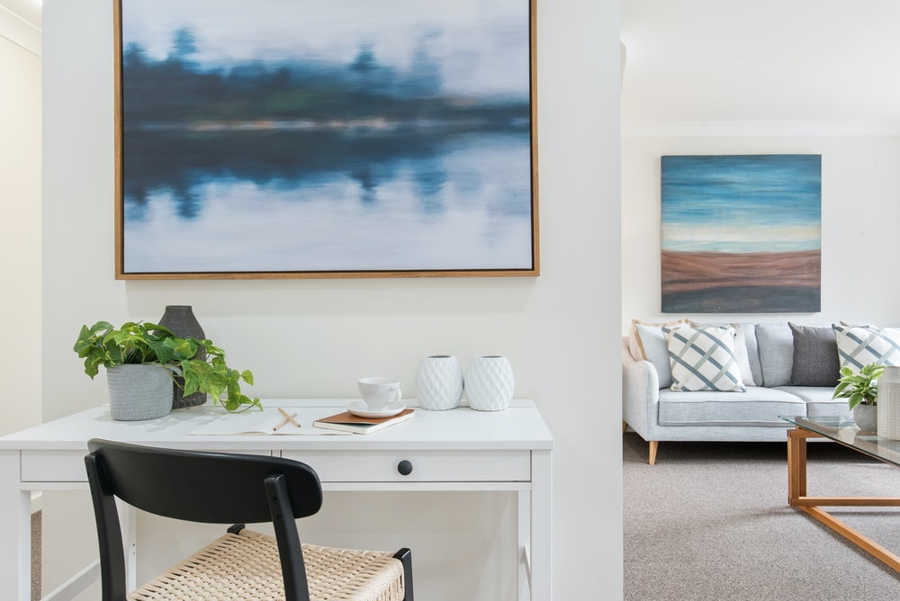 white and black table with chairs near body of water painting