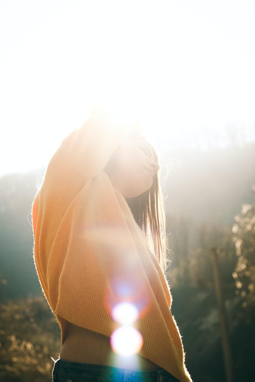 woman in orange hoodie standing during daytime
