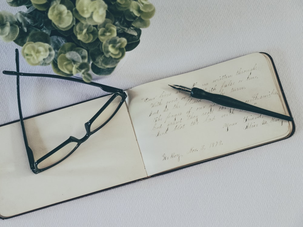 black framed eyeglasses on white paper