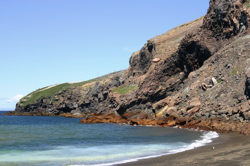 brown and green rock formation beside blue sea under blue sky during daytime