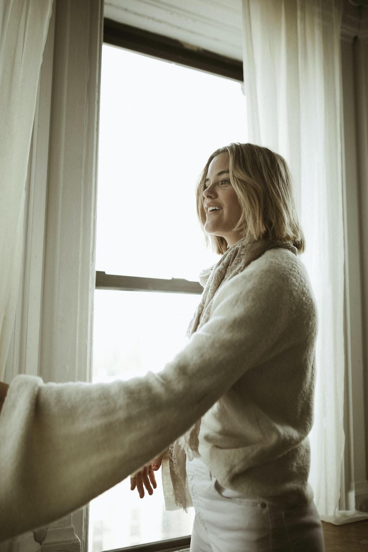 woman in white sweater standing beside window