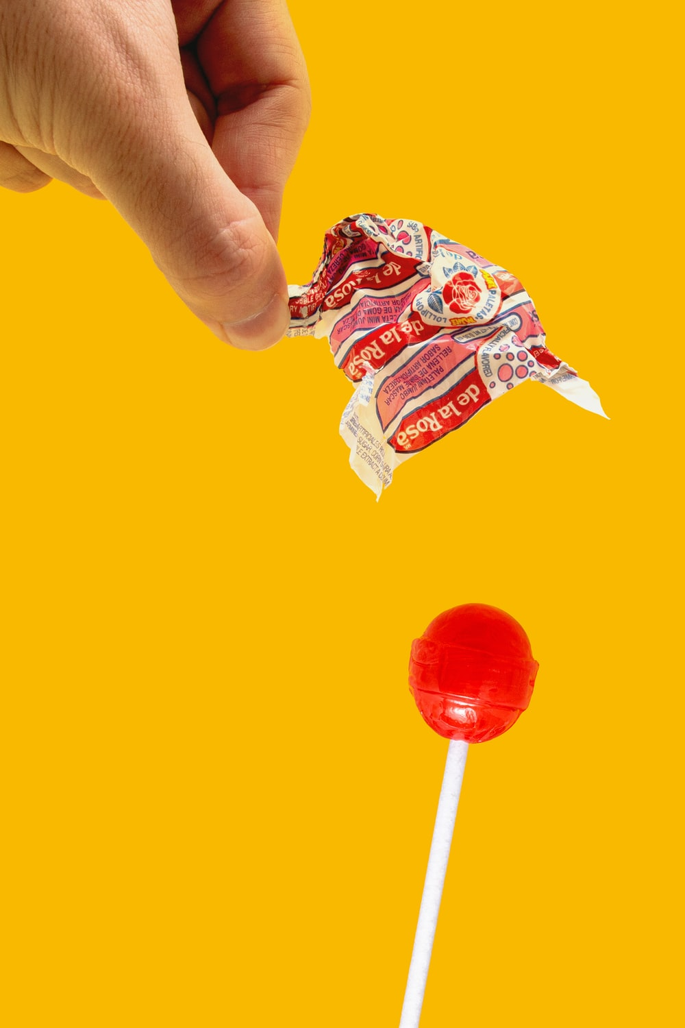 person holding red lollipop with blue and white candy wrapper