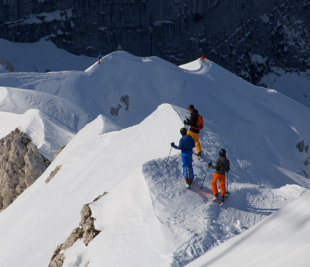 man in orange jacket and black pants on snow covered mountain during daytime