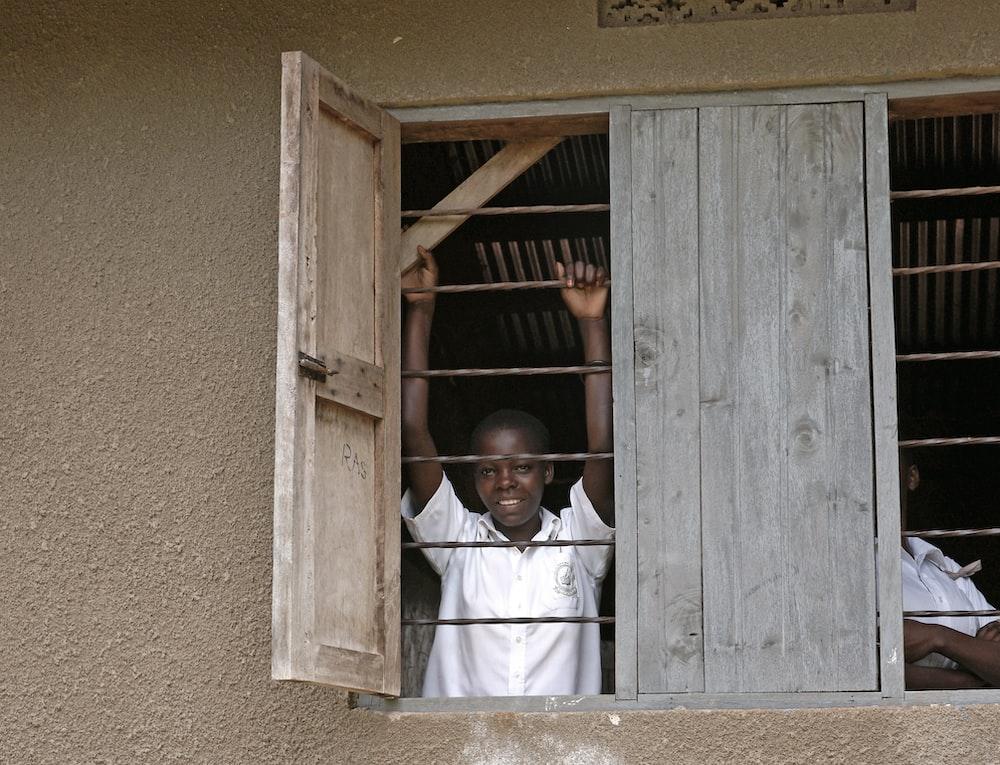man in white dress shirt standing in front of brown wooden door