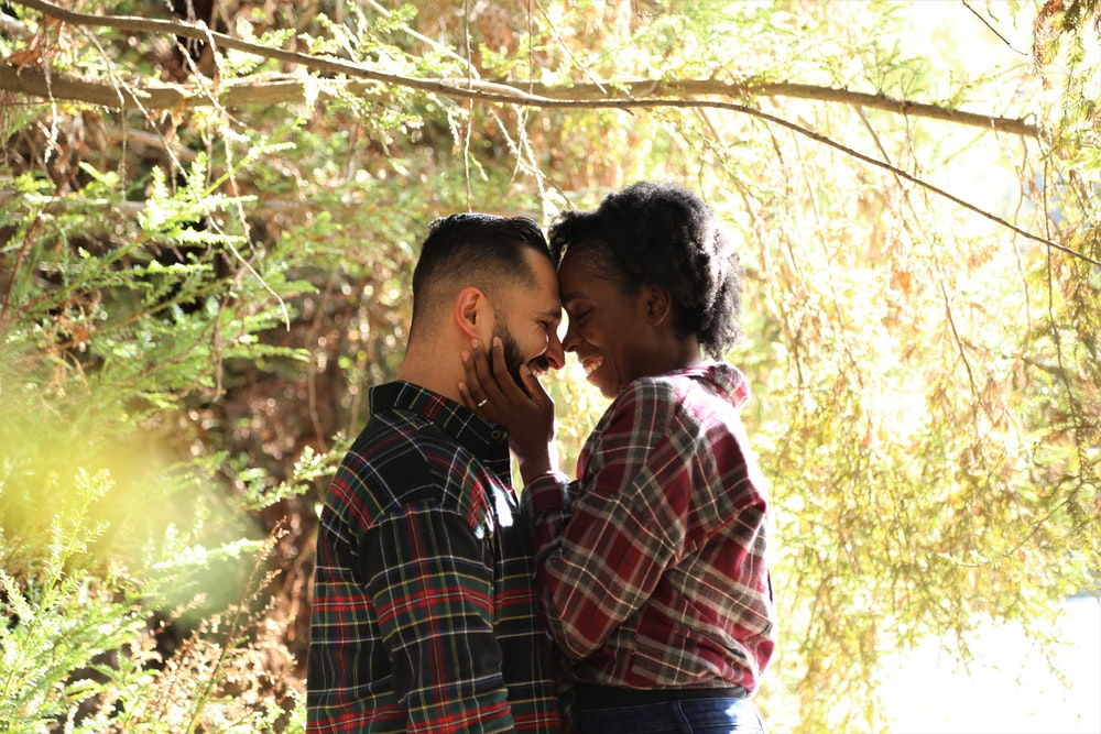 man in blue white and red plaid dress shirt kissing woman in white shirt