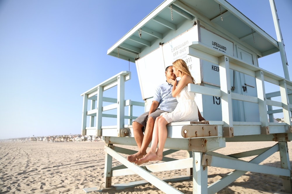 woman in white t-shirt sitting on brown wooden bench during daytime