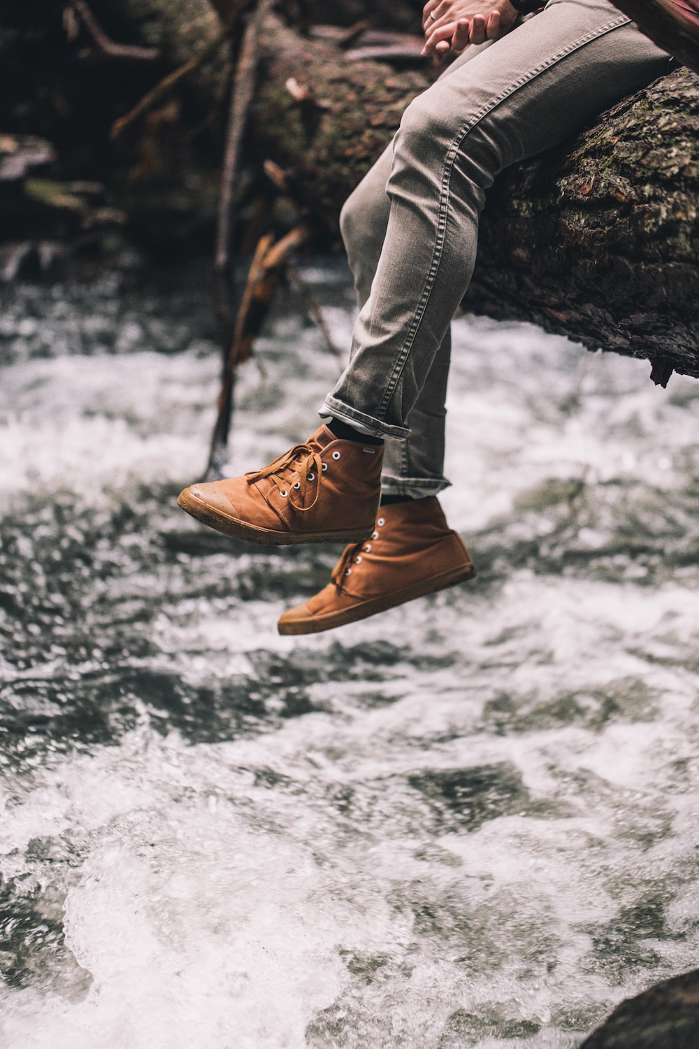 person in brown leather boots standing on rock in front of water