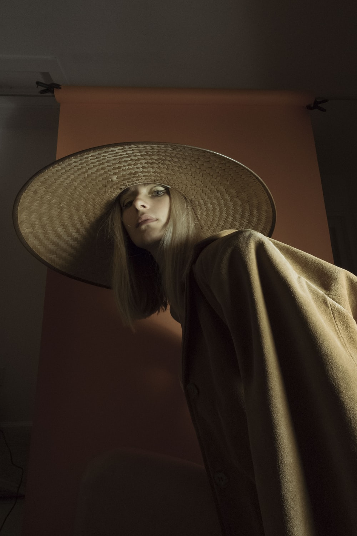 woman in brown coat wearing brown sun hat