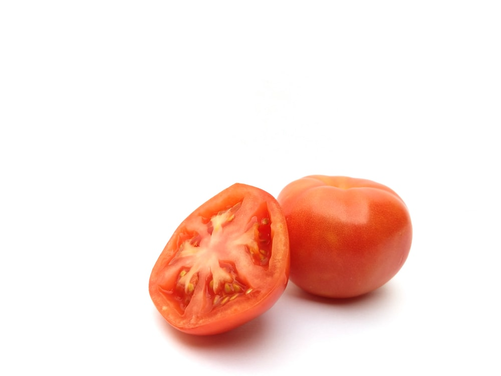 2 red round fruits on white surface