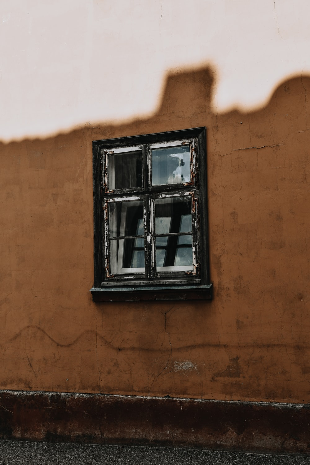 black wooden window frame on brown concrete wall