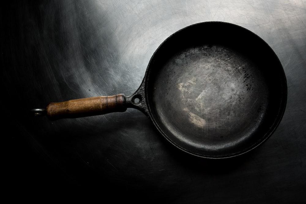 black frying pan on black surface