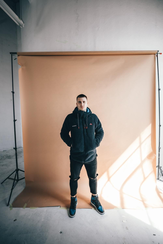 man in black jacket standing beside white wall