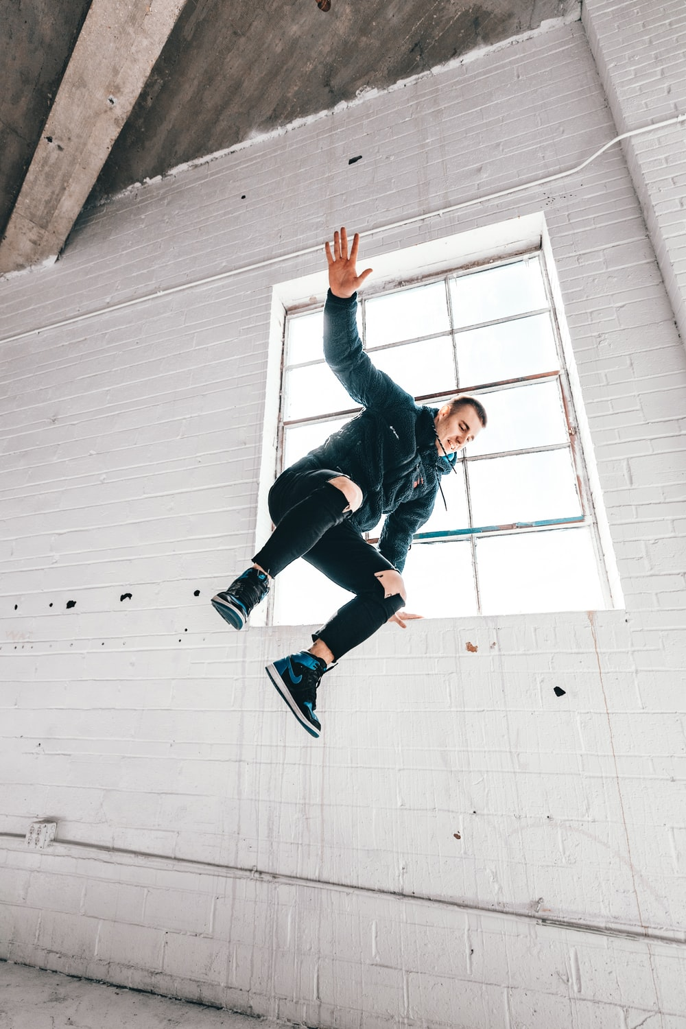 woman in black jacket and black pants jumping on white wall