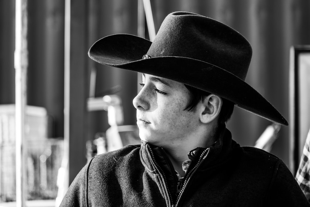 man in black cowboy hat in grayscale photography