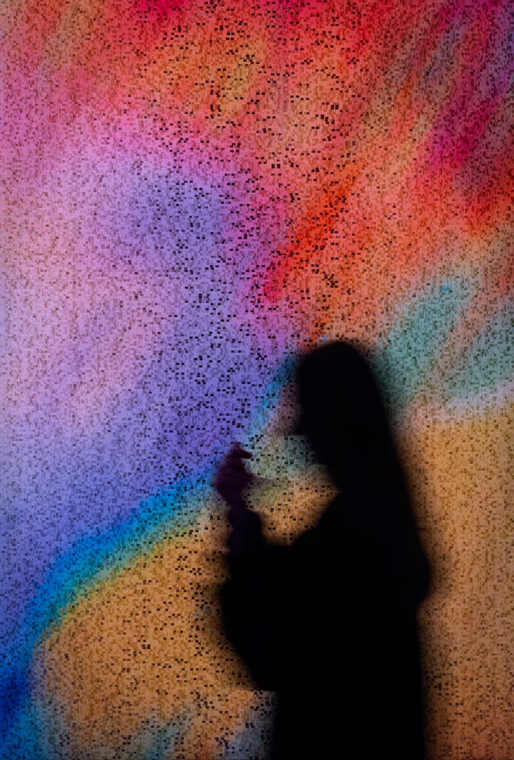 persons shadow on blue pink and green textile