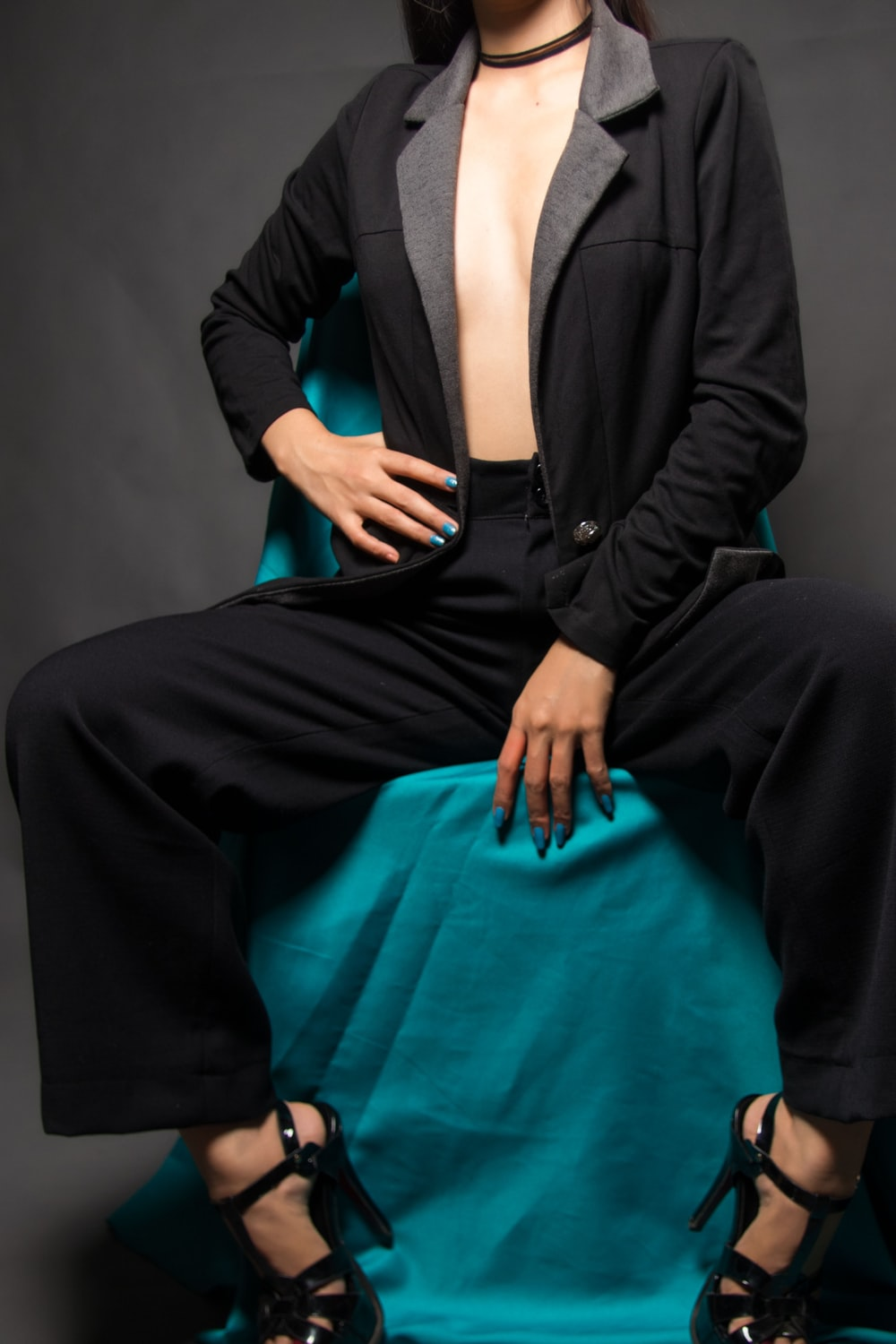 woman in black blazer and black dress pants sitting on blue chair