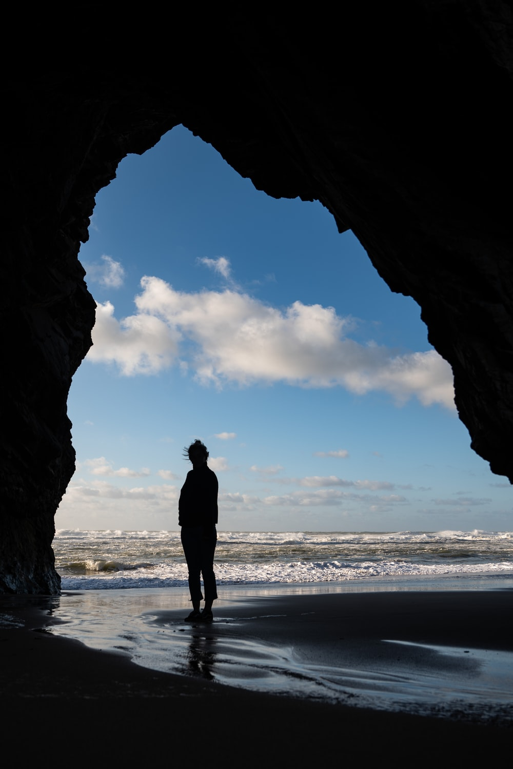 silhouette of man standing on seashore during daytime
