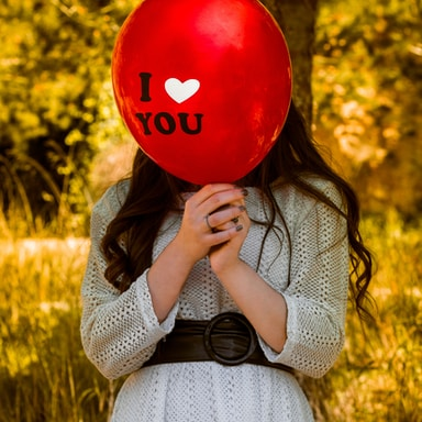 woman in gray sweater holding red balloon