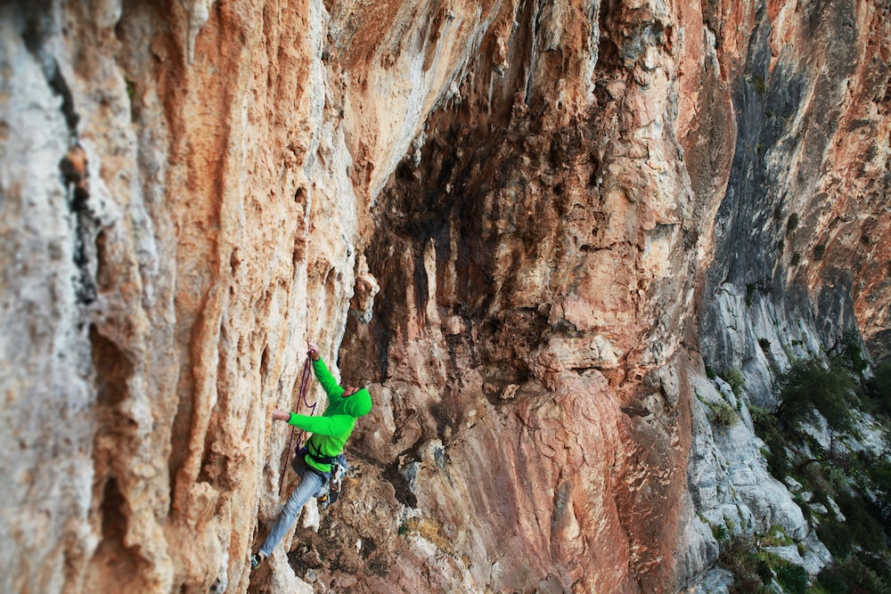 man in green jacket climbing on brown rock