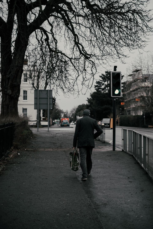 man in gray jacket walking on sidewalk during daytime