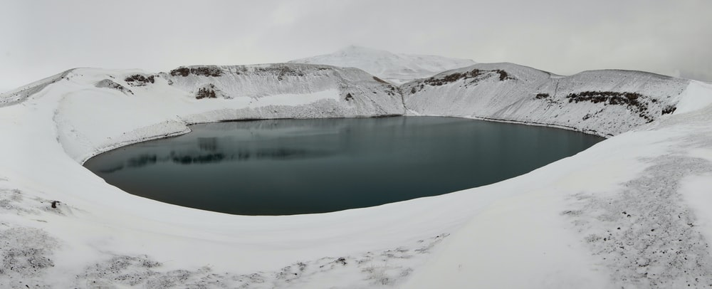 lake in the middle of snow covered mountains