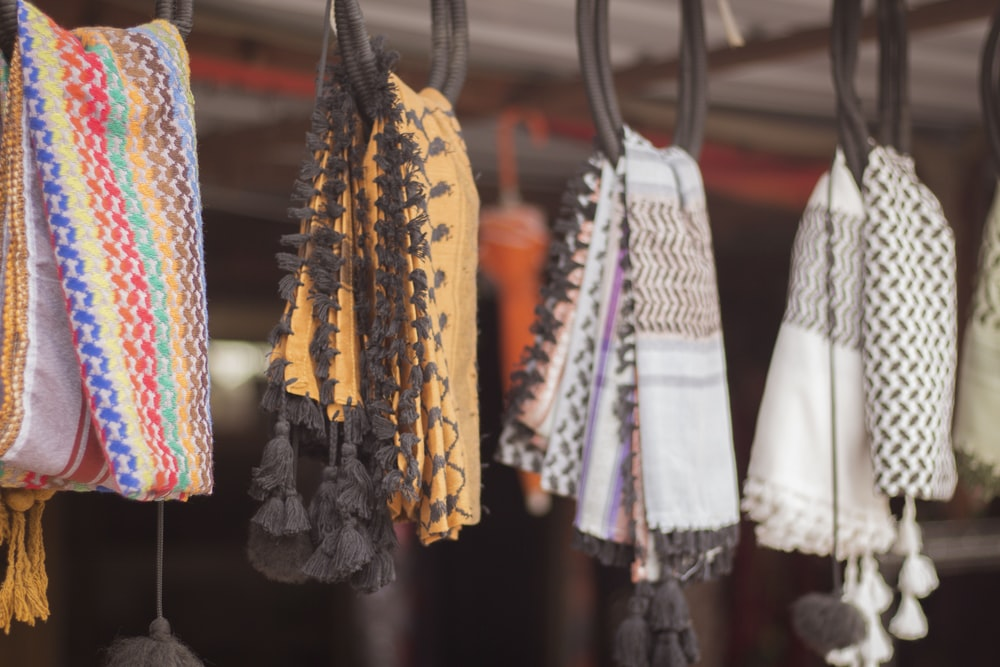 assorted color clothes hanged on black metal rack