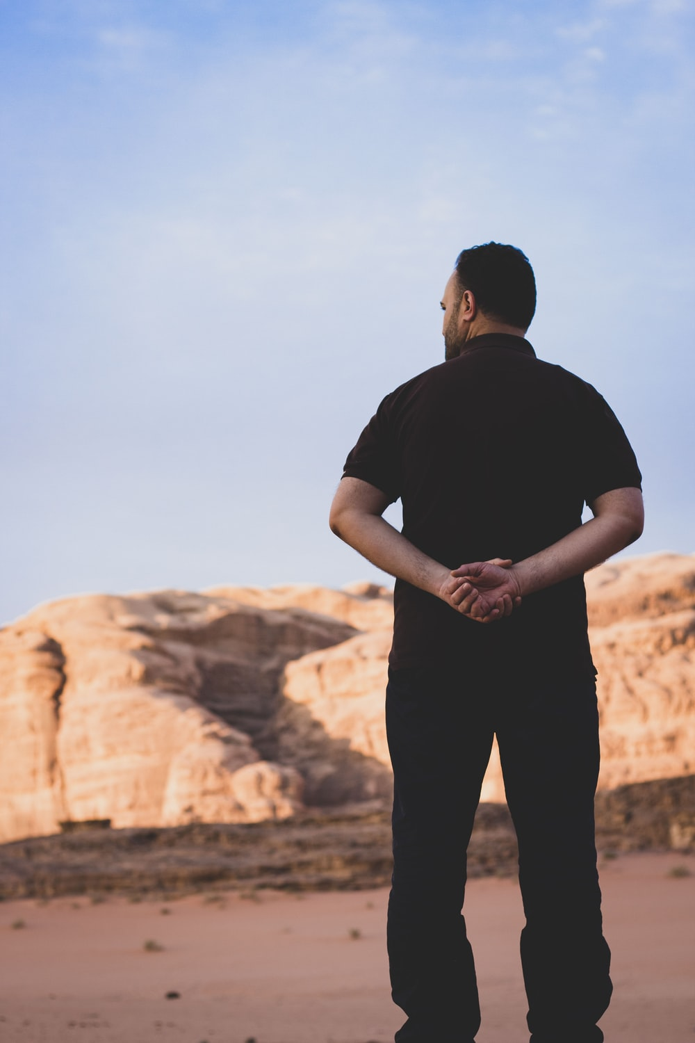 man in black t-shirt standing on brown rock formation during daytime