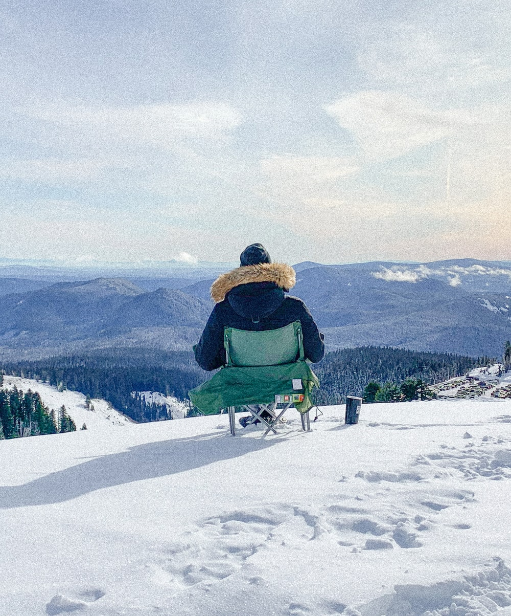 man in green jacket sitting on green chair on snow covered ground during daytime