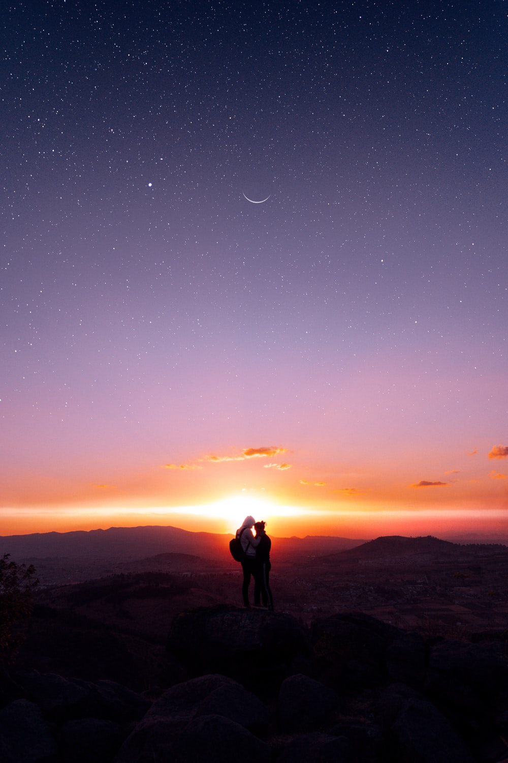 silhouette of man and woman standing on top of mountain during night time