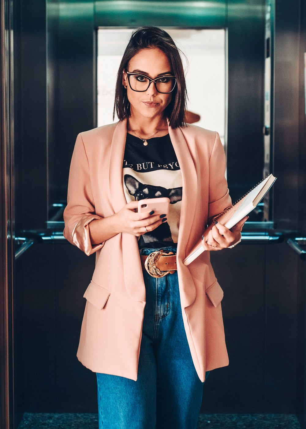 woman in brown blazer holding book