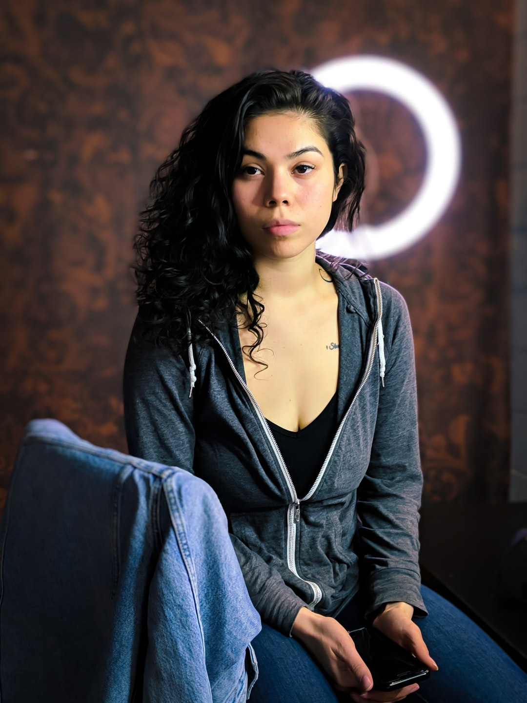 Native American Woman in a hoodie Sitting in front of a ring light and rust colored background, with a jean jacket on the chair back.