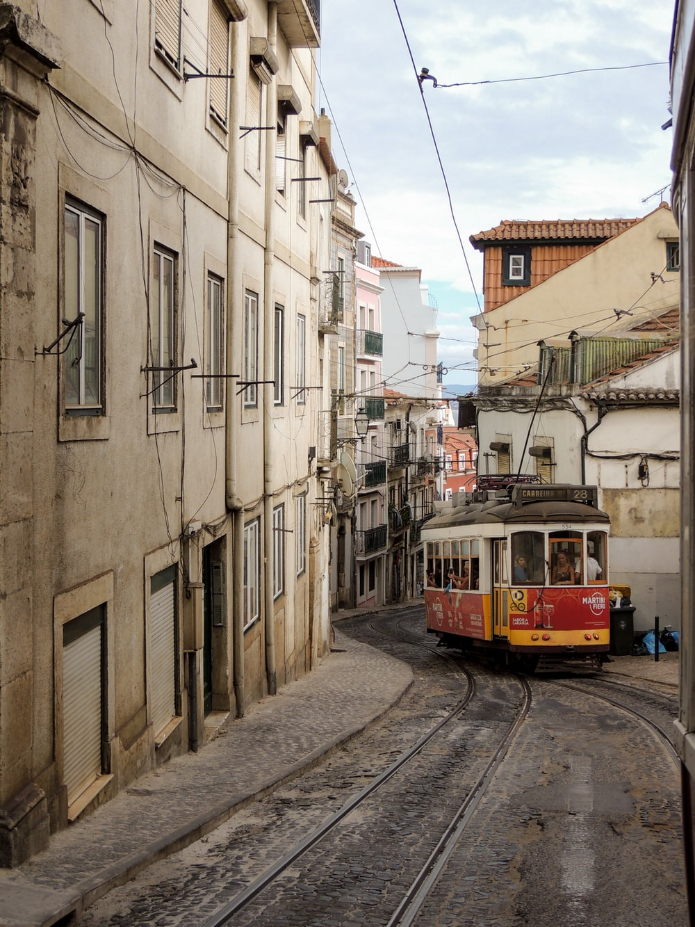 red and white tram on road between buildings during daytime